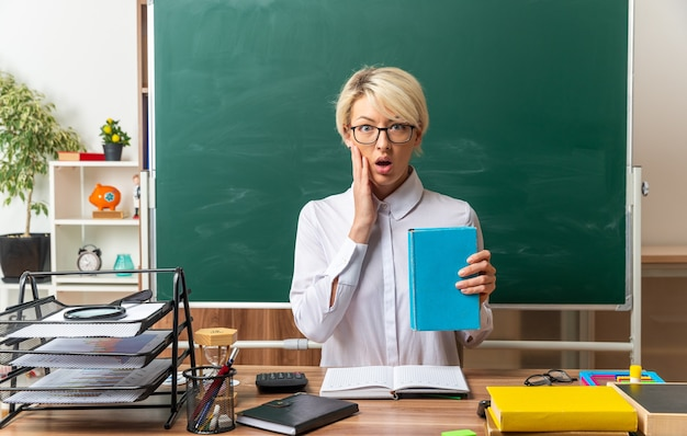 Preocupada jovem loira professora usando óculos, sentada na mesa com o material escolar na sala de aula, mostrando o livro fechado, mantendo as mãos no rosto, olhando para a frente