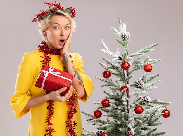 Preocupada jovem loira usando coroa de flores de natal e guirlanda de ouropel em volta do pescoço em pé perto de uma árvore de natal decorada, olhando segurando um pacote de presente, mantendo as mãos no rosto, isolado na parede branca