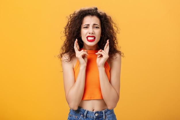 Preocupada, preocupada garota urbana elegante com penteado encaracolado e batom vermelho cerrando os dentes cruzando os dedos para dar sorte e franzindo a testa, sentindo-se nervosa e ansiosa posando com problemas na parede laranja.