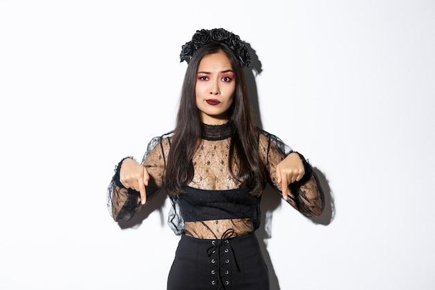 Preocupada, uma mulher asiática desapontada em um vestido de renda preta e grinalda sorri cética enquanto aponta o dedo para algo ruim, reclamando sobre fundo branco.