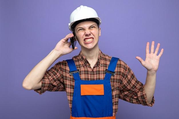 Preocupado ao mostrar cinco jovens construtor do sexo masculino vestindo uniforme falando ao telefone