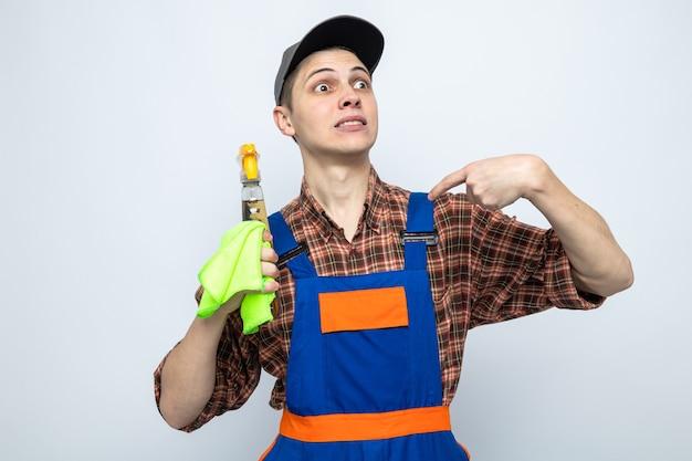 Preocupado aponta para si mesmo, jovem faxineiro vestindo uniforme e boné segurando um pano com agente de limpeza