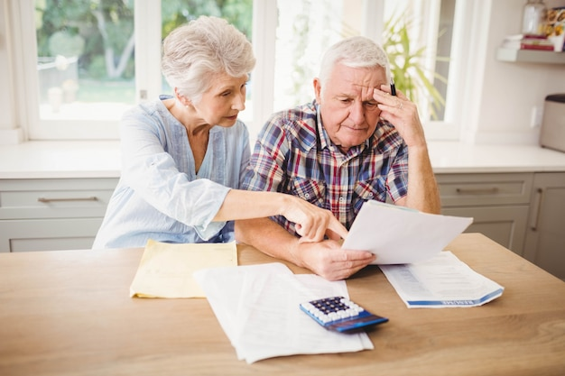 Preocupado casal sênior, verificando suas contas em casa