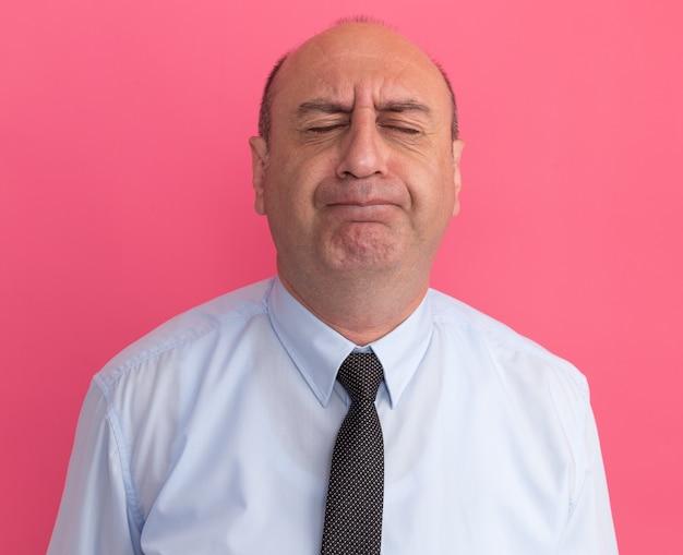 Preocupado com os olhos fechados, homem de meia-idade vestindo camiseta branca com gravata isolada na parede rosa