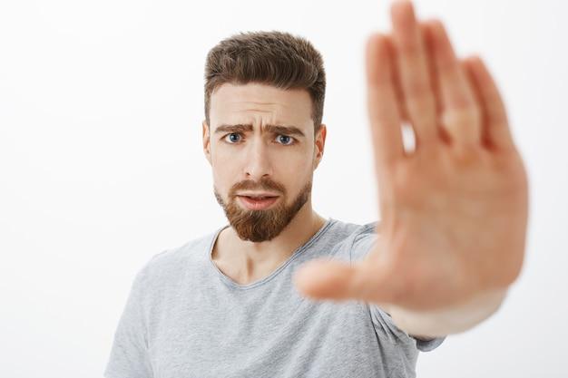 Preocupado e preocupado jovem amigo do sexo masculino com olhos azuis, barba e bigode puxando a palma da mão para avisar e parar de fazer escolhas erradas, carrancudo, ansioso, preocupado com o companheiro