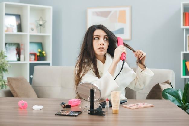 Preocupado em alisar o cabelo com chapinha jovem sentada à mesa com ferramentas de maquiagem na sala de estar