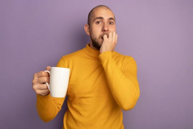 Preocupado em olhar para a frente, jovem bonito segurando uma xícara de chá, morde as unhas isoladas em roxo com espaço de cópia
