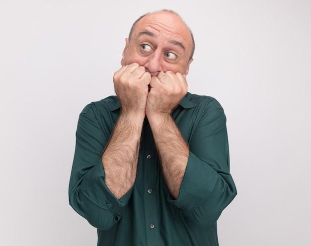 Preocupado em olhar para o lado de um homem de meia-idade vestindo uma camiseta verde, morde as unhas isoladas na parede branca com espaço de cópia