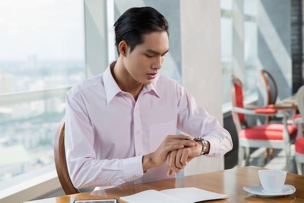 Preocupado homem asiático novo que olha o relógio em cafe