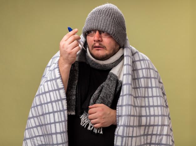 Preocupado homem doente de meia-idade usando chapéu de inverno e lenço embrulhado em xadrez segurando e olhando para o termômetro isolado na parede verde oliva