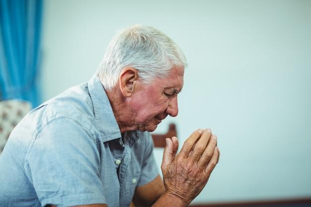 Preocupado homem idoso sentado na sala de estar