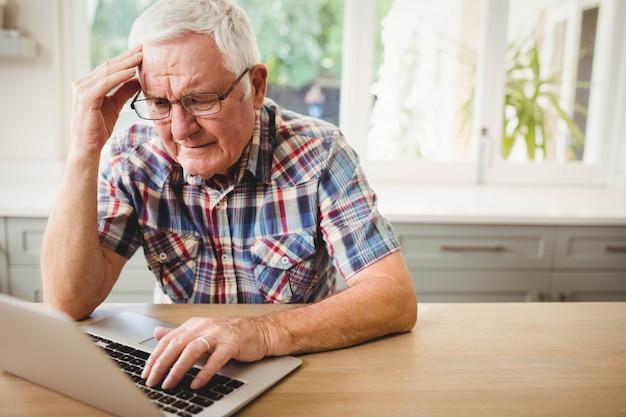 Preocupado homem sênior usando laptop em casa