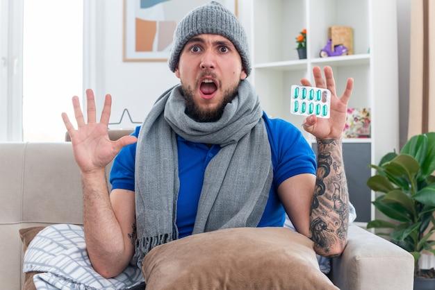 Preocupado, jovem, doente, usando cachecol e chapéu de inverno, sentado no sofá na sala de estar com o travesseiro nas pernas, mostrando o pacote de cápsulas e a mão vazia olhando para frente com a boca aberta