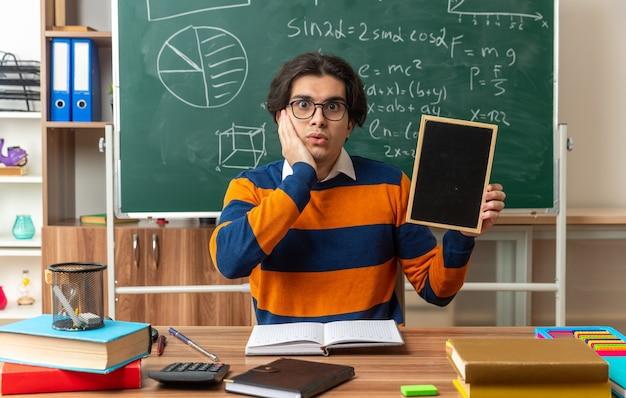 Preocupado, jovem professor de geometria usando óculos, sentado na mesa, com o material escolar na sala de aula, mostrando uma minilousa com as mãos no rosto, olhando para a frente
