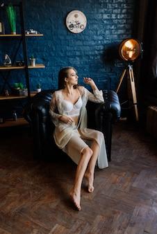 Preparação da manhã da noiva. mulher jovem e bonita em roupão de casamento branco em um estúdio escuro