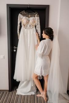 Preparação da manhã de casamento. noiva linda fica perto de seu vestido de noiva. retrato de manhã noiva