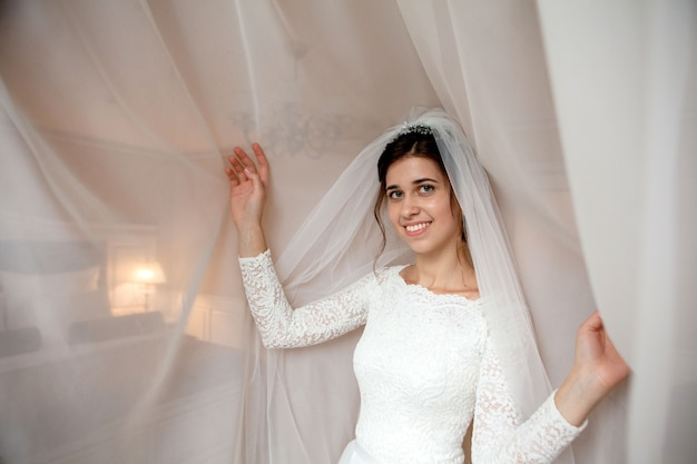 Preparação da manhã de noiva. noiva linda em lingerie branca de casamento perto da janela do quarto