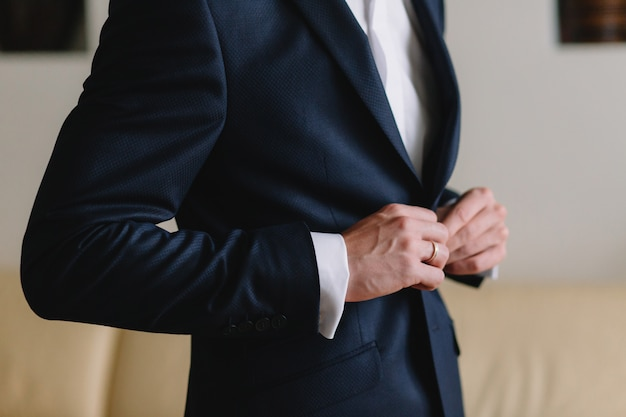 Preparação da manhã do casamento do noivo. noivo novo e considerável que começ vestido em uma camisa do casamento.