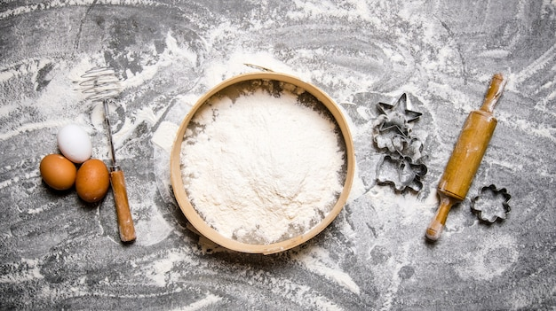 Preparação da massa. ingredientes para a massa - farinha na peneira, ovos e rolo com formas. na mesa de pedra. vista do topo