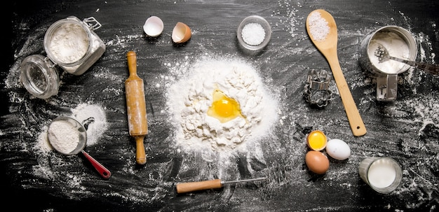 Preparação da massa. ingredientes para a massa - farinha, ovos e ferramentas - rolo, peneira, batedor. sobre um fundo preto de madeira. vista do topo