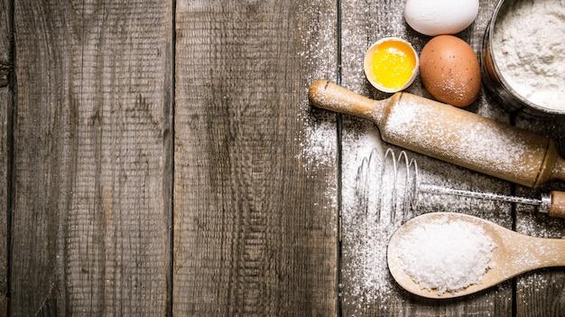 Preparação da massa. ingredientes para a massa - ovos e farinha com rolo. em fundo de madeira. espaço livre para texto. vista do topo