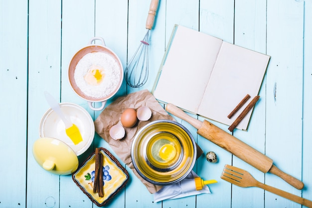 Preparação da massa. ingredientes para a massa - ovos e farinha com rolo. em fundo de madeira.