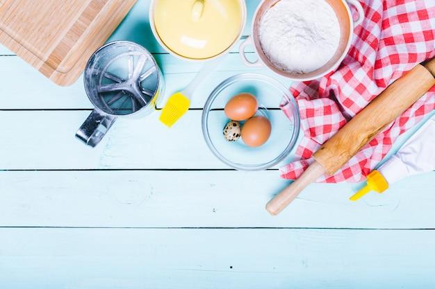 Preparação da massa, ingredientes para a massa - ovos e farinha com um rolo, na superfície de madeira,