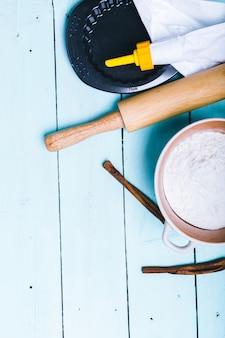 Preparação da massa. ingredientes para a massa - ovos e farinha com um rolo. no fundo de madeira.