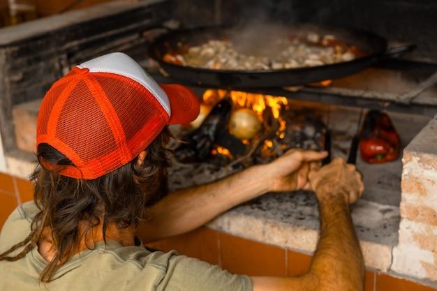 Preparação das brasas da paella valenciana com brasas e legumes