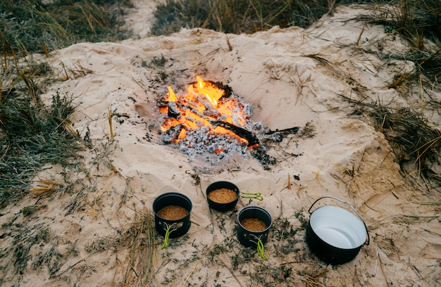 Preparação de alimentos em viagem de acampamento. cozinhando na fogueira na natureza selvagem na praia de nevoeiro perdida em dunas de areia além do oceano.