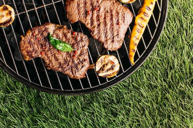 Preparação de bife grelhado e legumes na churrasqueira sobre tapete de grama