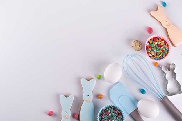Preparação de biscoitos de gengibre. biscoitos de páscoa em forma de um coelho engraçado, ferramentas necessárias para fazer bolos de gengibre, granulado colorido. conceito de páscoa