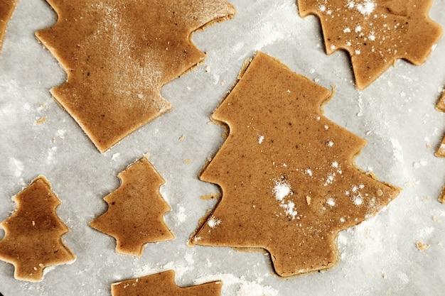 Preparação de biscoitos de gengibre. corte figurado biscoitos em forma de árvore de natal. símbolo de véspera de ano novo.