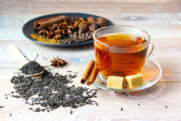 Preparação de chá de masala em um copo de vidro com açúcar e especiarias no fundo de madeira