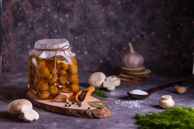 Preparação de cogumelos champignon fermentados em conserva com folha de louro, pimenta, sal, alho e endro em um frasco de vidro em uma estante de madeira em um ambiente discreto