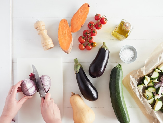 Preparação de comida vegan, vegetais crus diferentes batata doce, tomate cereja, abóbora e abóbora, mãos de mulher cortando cebola