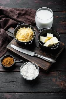 Preparação de conjunto de molho branco de queijo bechamel, sobre velha mesa de madeira escura