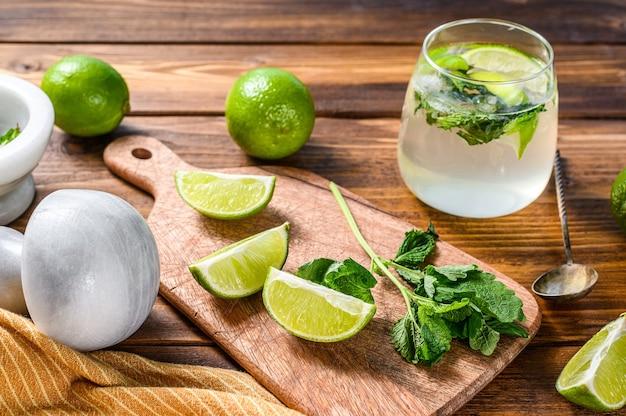 Preparação de coquetéis mojito. ingredientes menta, limão, gelo e utensílios de bar.
