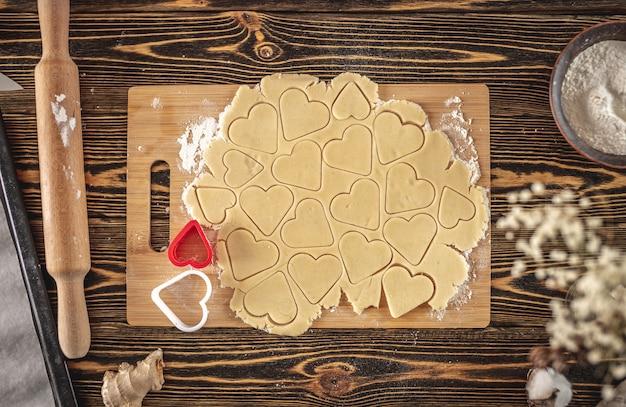 Preparação de deliciosos biscoitos caseiros em forma de coração em uma mesa de madeira