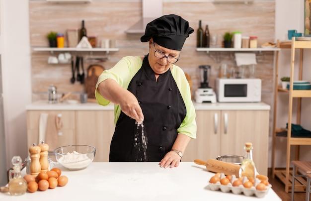 Preparação de deliciosos biscoitos na cozinha de casa pelo chef de avental