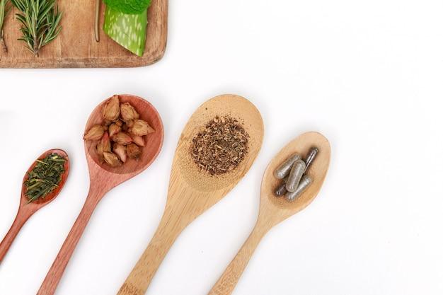 Preparação de ervas medicinais com ervas frescas e flores secas e almofariz com pilão.