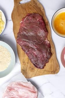 Preparação de escalope de vitela milanesa tradicional caseiro com farinha, ovo, pão ralado, queijo e fiambre