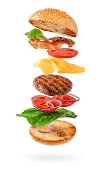Preparação de hambúrguer maxi com ingredientes voadores isolados no branco