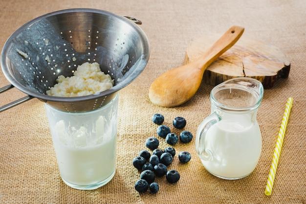 Preparação de iogurte de kefir com frutas vermelhas, mirtilos frescos, saudáveis e naturais.