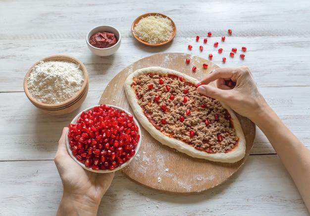 Preparação de pizza árabe tradicional manaqish com carne e romã.