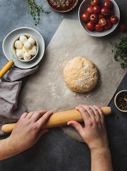 Preparação de pizza. massa de grãos inteiros em assadeiras com vários ingredientes para cozinhar pimenta, mussarela, tomate, molho de tomate, tomilho.