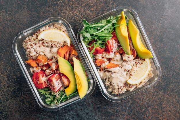 Preparação de refeição saudável vegetariana dentro de recipientes. vegetais crus e quinoa para o almoço em uma mesa escura.