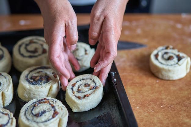 Preparação de rolos de canela. uma mulher coloca pães em uma assadeira.