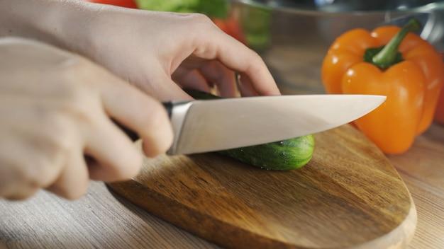 Preparação de salada de legumes cortada em madeira, cortando as mãos das mulheres, cortando pepino em formato grande.