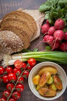 Preparação de sanduíches de verão queijo cottage com cebolinha, rabanetes e tomates. dieta ceto, batatas fritas inteiras. estilo de vida saudável.